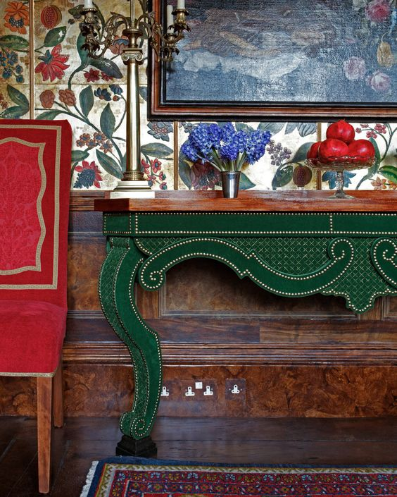 Red upholstered chair and an emerald console table