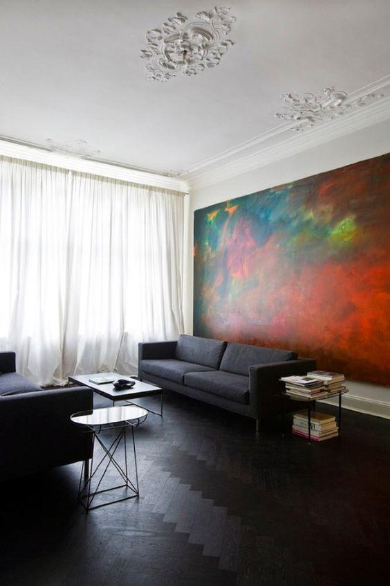 dark wood herringbone floors and charcoal grey sofas show off the oversized art piece
