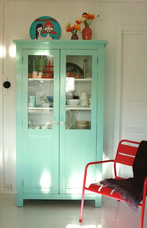 Neutral interior with a mint cupboard and a statement red chair
