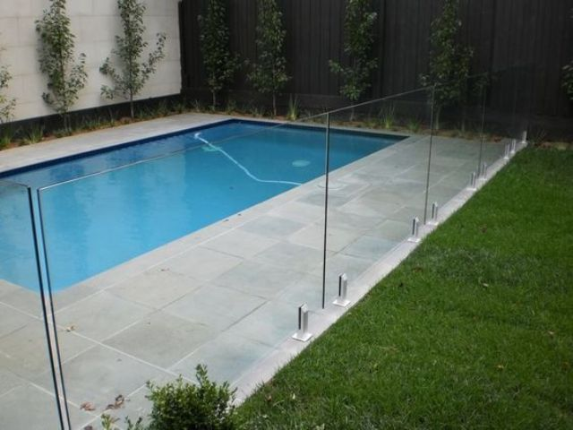 stone pavers deck and a glass fence for a pool