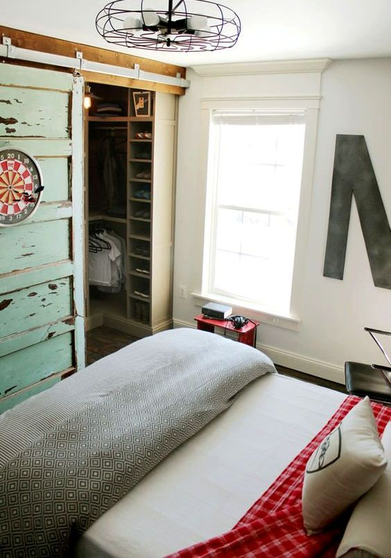 a closet in a bedroom behind sliding barnwood doors