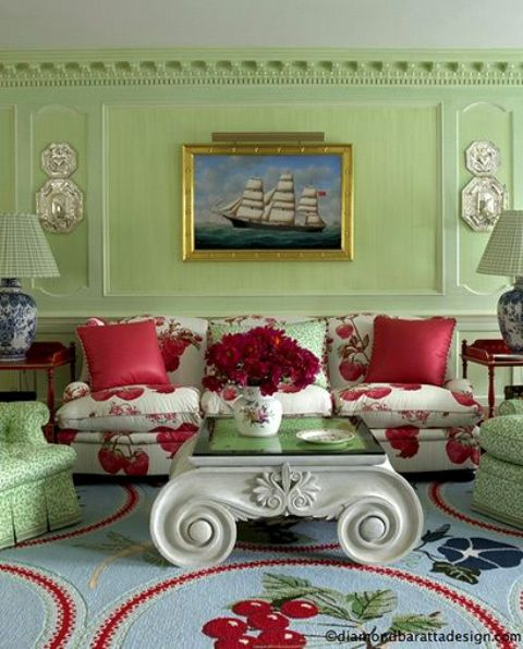 Soft Green Room Decor Accentuated With Red Rugs And Pillows