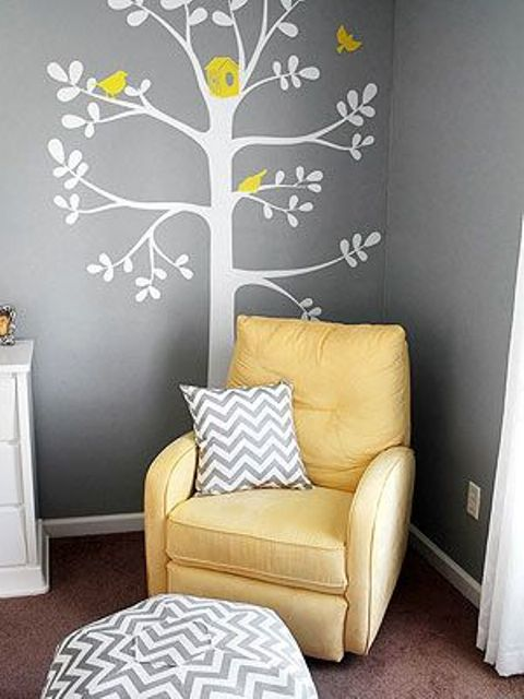 parent nook with a bold yellow chair and an applique on the wall