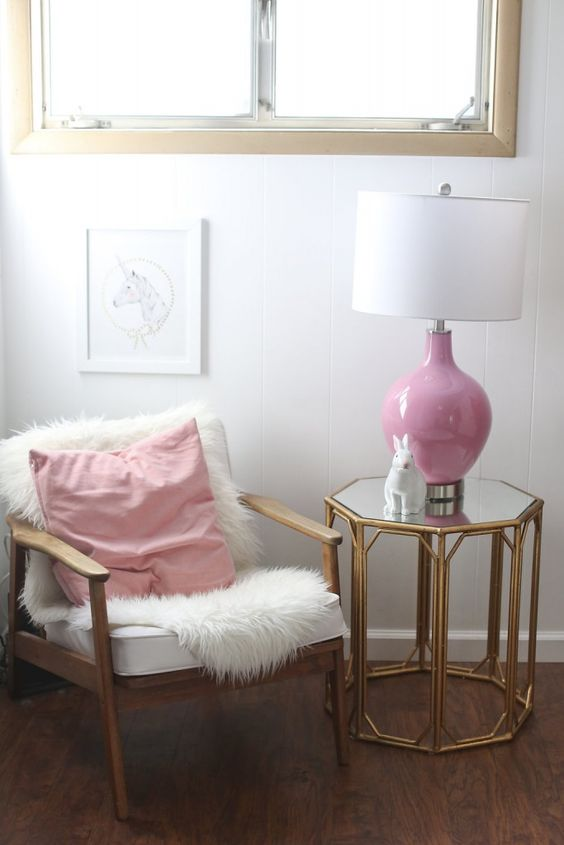 glam nursery seating area with a fur cover and a pink lamp