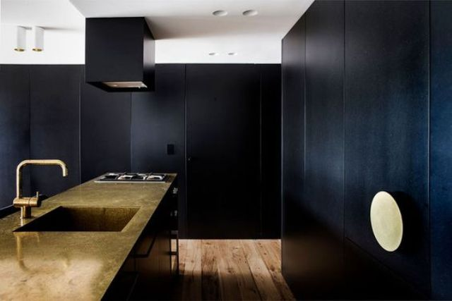 black kitchen clad with textured panels and a copper kitchen island