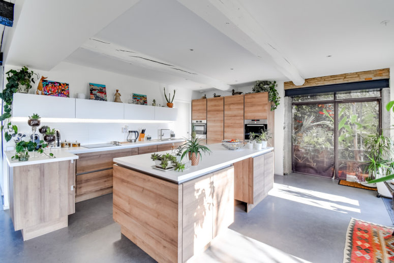 polished concrete grey flooring on a spacious kitchen with wooden cabinets (JACQUES AGRAFFEIL- MAÎTRISE D'ŒUVRE)