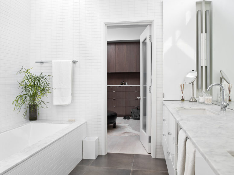 a pure white bathroom with dark gray flooring (Searl Lamaster Howe Architects)