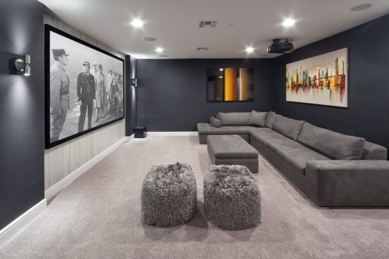 a home theater with a gray sectional couch and a gray carpet that reflect less light than white ones (Morrone Interiors)
