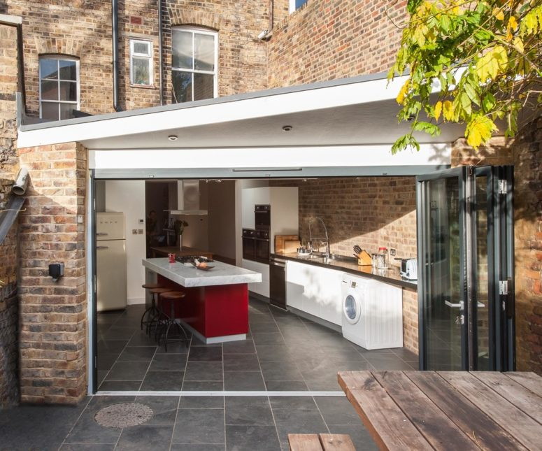 dark gray tiles are perfect for an indoor-outdoor kitchen because they won't be damaged by any weather conditions (Architect Your Home)