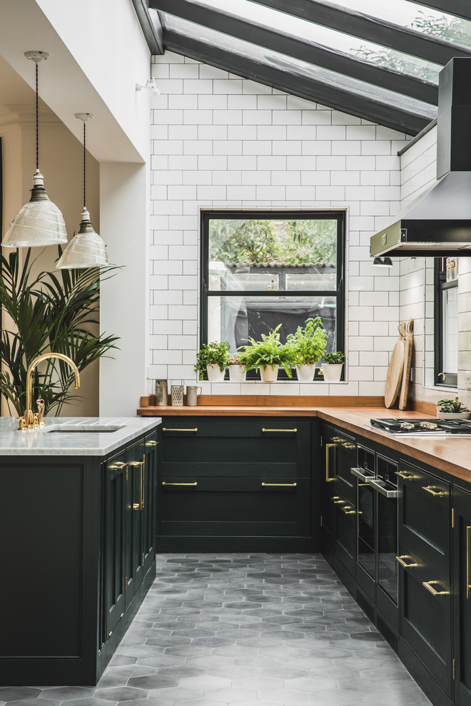whitewash-inspired hexagonal tiles on a traditional kitchen with black cabinets (Lukonic)