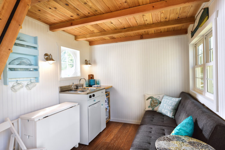 this beach cottage features different space saving solutions like a mini fridge, a sectional sofa and an IKEA's folding dining table that can seat 4 comfortable (Tiny Digs)