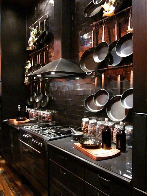 moody black kitchen with reddish tiles backsplash