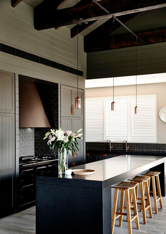 moody kitchen with dark panelled cabinetry and leather pulls
