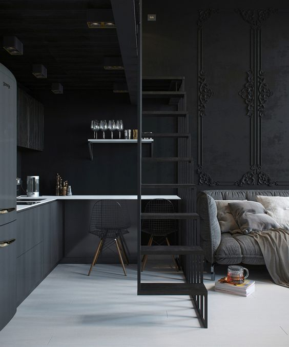 tiny black paneled kitchen under the stairs