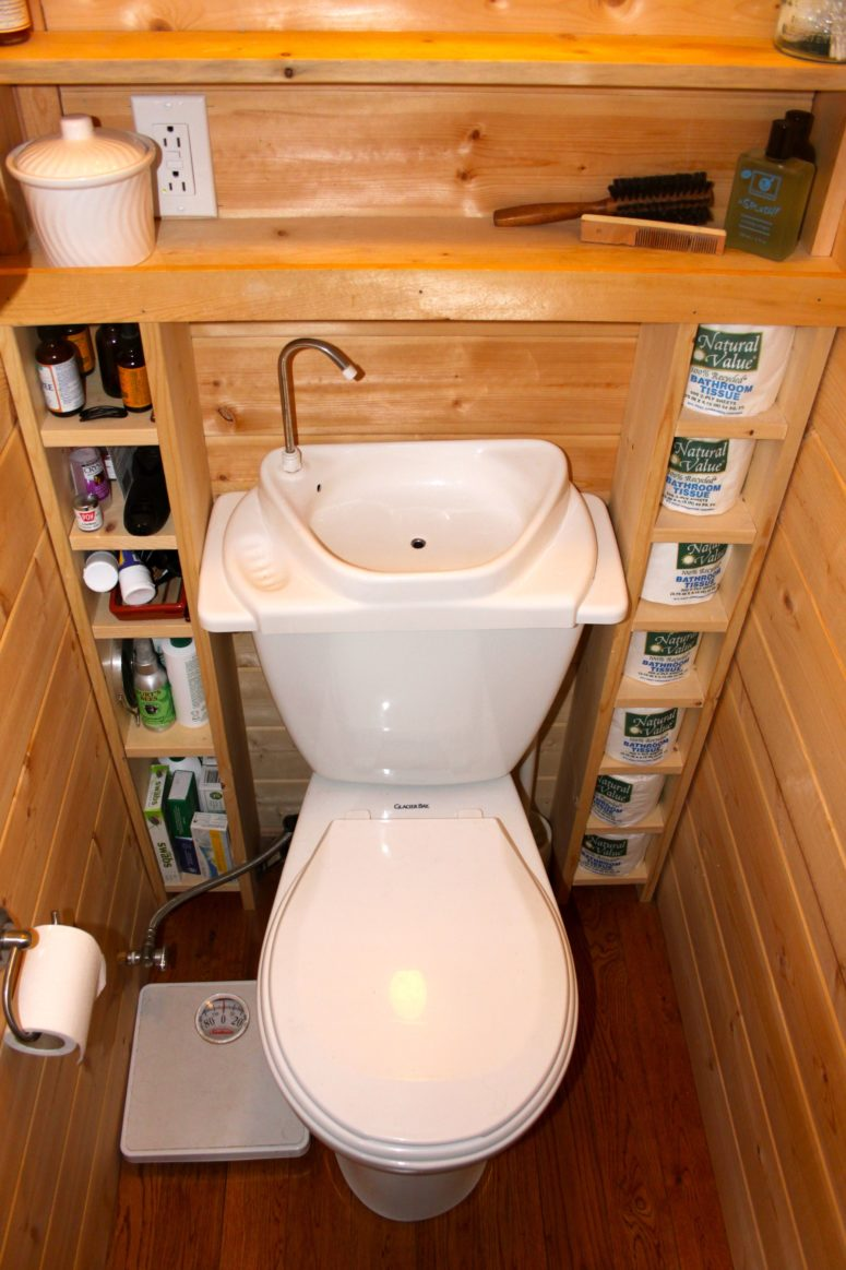 a tiny cottage bathroom that features a porcelain toilet/sink combo and an open shelving unit