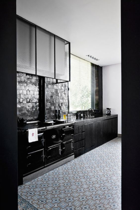 wooden black kitchen with a brick backsplash and a glass hood