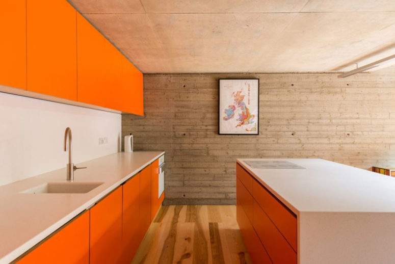 The kitchen is designed in bold orange, the space is minimal and uncluttered, everything is hidden