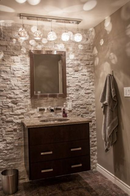 Grey Powder Room With A Stone Accent Wall And A Modern Dark Wood Vanity