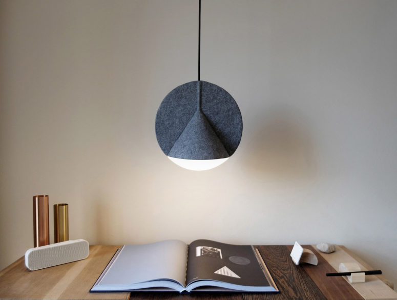 The lamp reminds of a flat disc bisecting a wide, three-dimensional cone