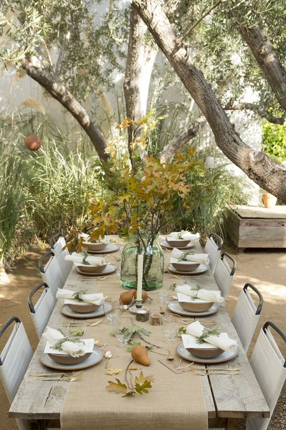 neutral table with a burlap table runner, fall leaves in a jar, pears and greenery