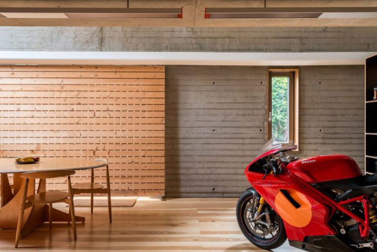 The dining area is clad with light warm-colored wood, and the dining set is also of the same wood