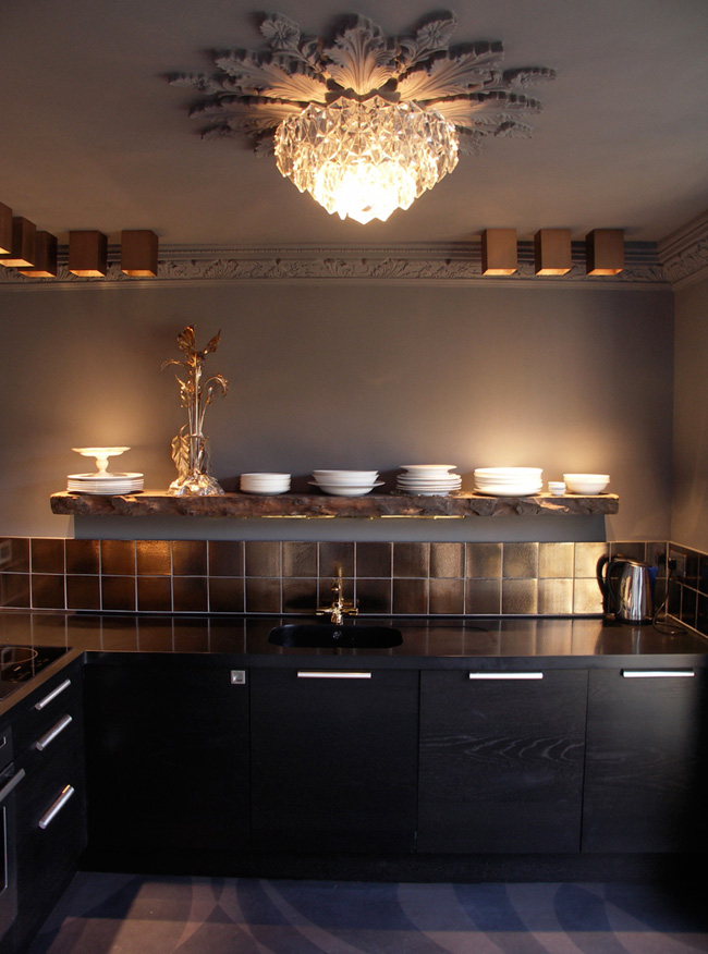 The kitchen is modern, it's black cabinets and tiles contrast with a vintage chandelier