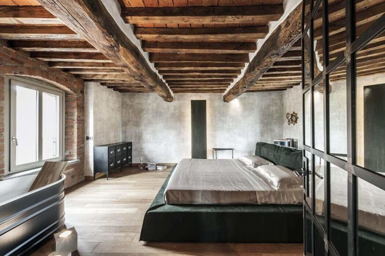 The master bedroom boasts of original ceilings with wooden beams and  industrial touches