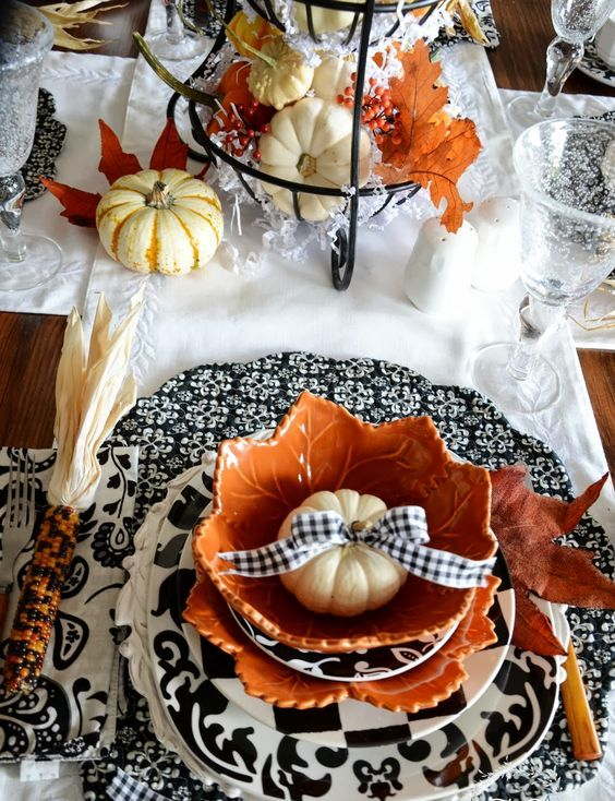 patterned black and white chargers, pumpkins with a black and white bow, pumpkins in a wire stand