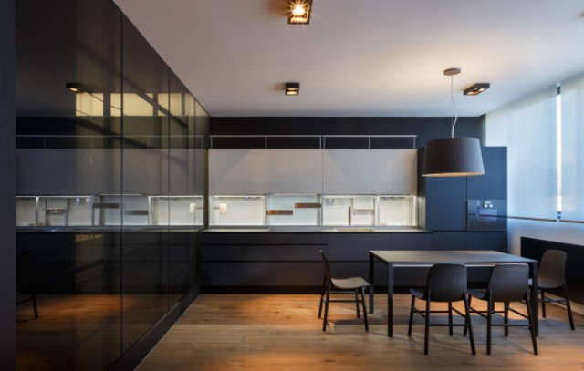 The smooth, dark cabinets match the dining table and chairs