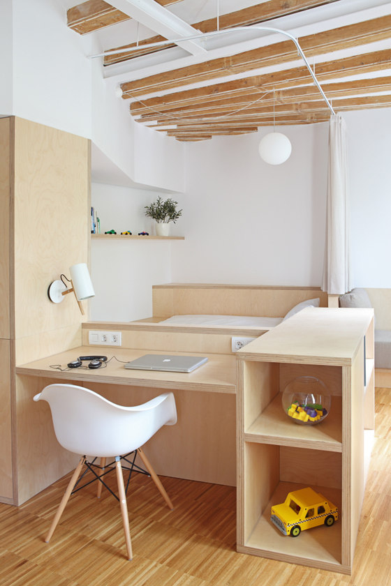 Most of furniture is made of light-colored wood. Bedroom is combined with a small but practical home office.