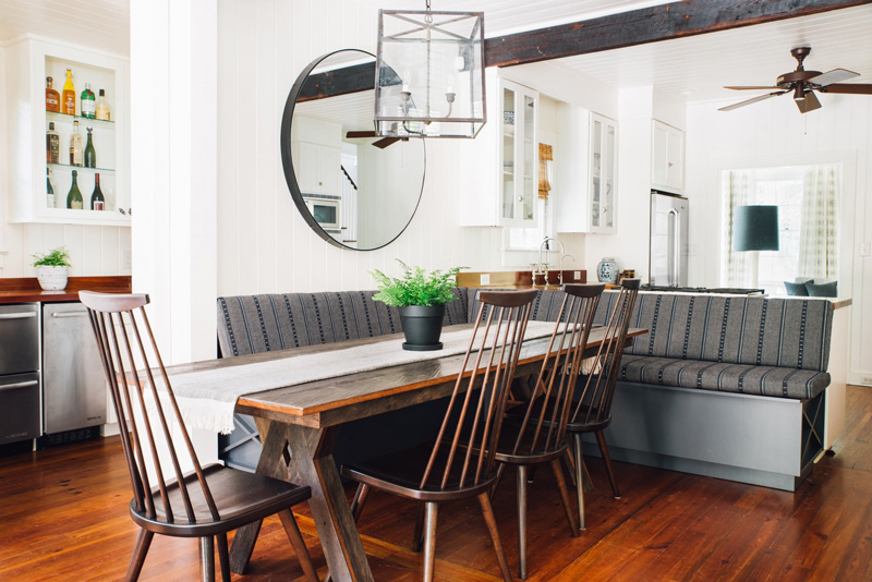 The breakfast nook is decorated dark, rustic and vintage
