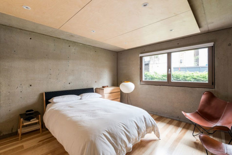 The guest bedroom is decorated with concrete and warm-colored wood, it's very laconic