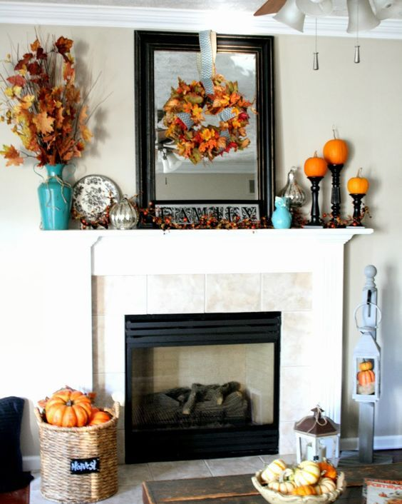 fall leaf wreath and bouquet in a vase, pumpkins on stands and a large framed mirror