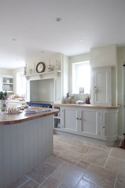 stone floors creates a modern feeling in this traditional kitchen