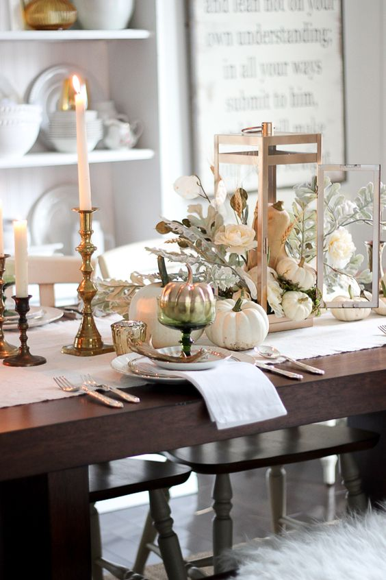 white and ivory table setting with gilded candle holders and silver pumpkins