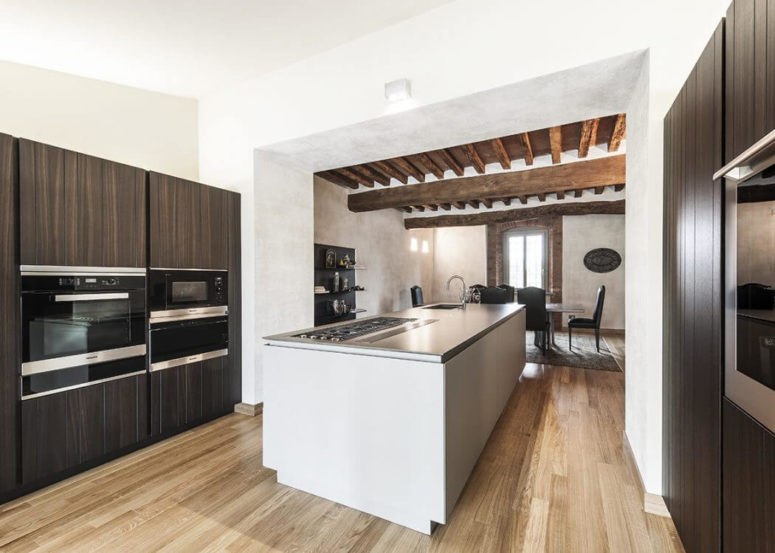 Kitchen cabinets are clad with dark wood, which contrasts with stainless steel appliances