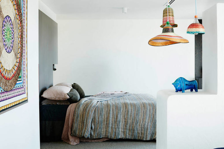 The bedroom space has an ethnic flavor with these textiles and woven lamps