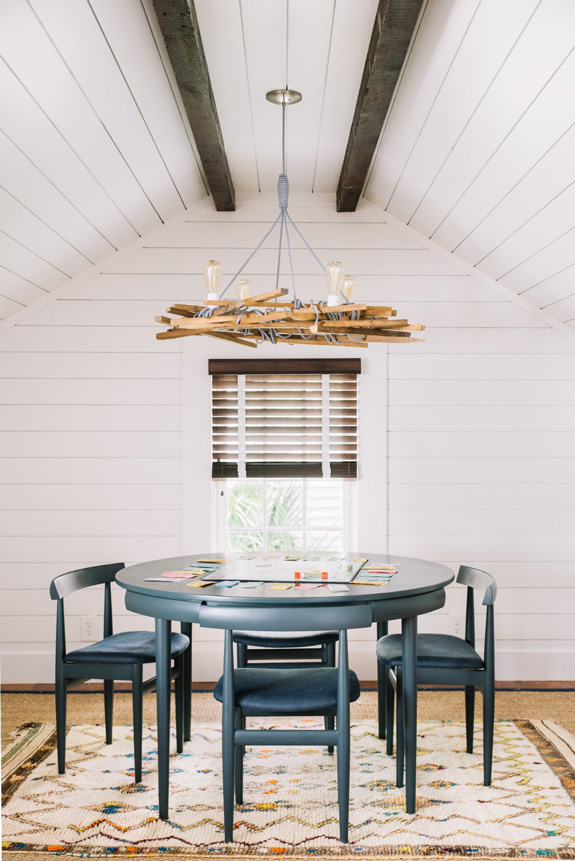 The dining zone is accentuated with a whimsy chandelier made of wood, rope and bulbs