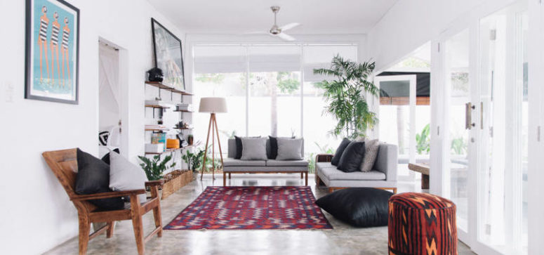 The lounge space is decorated with a bold rug and lots of island potted greenery