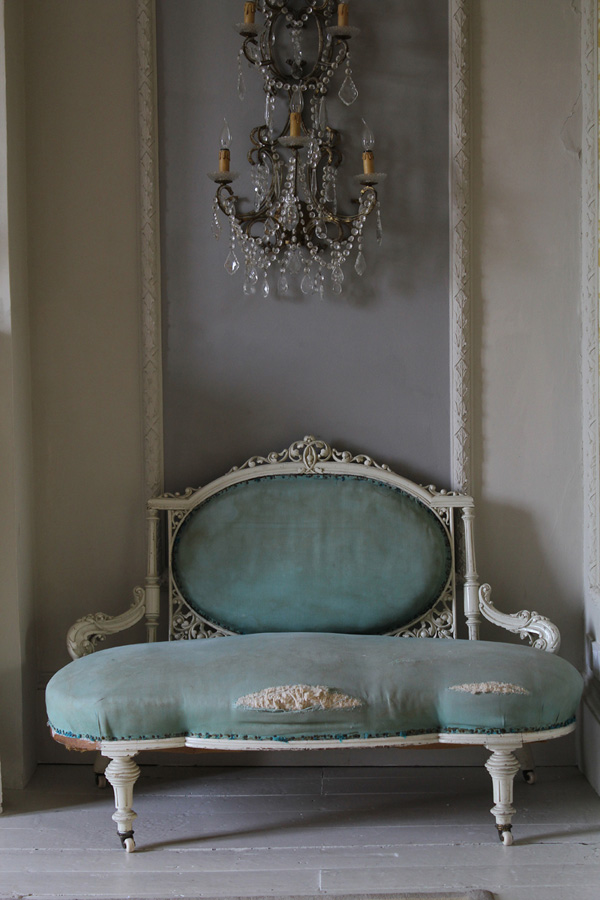 This green love seat is shabby chic, and it looks amazing with a vintage chandelier
