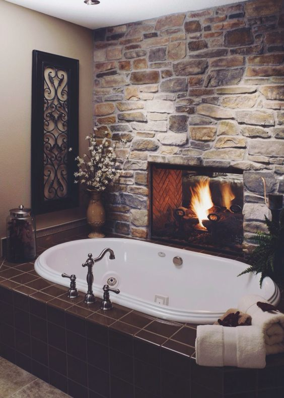 Rough Stone Wall With A Fireplace Makes A Bathroom Inviting