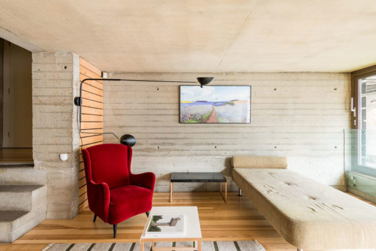 Concrete walls and wooden floor look contrasting with bold red chairs