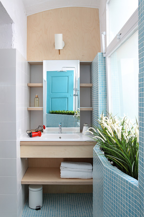 The bathroom is fully clad with small blue tiles and there's a lot of greenery