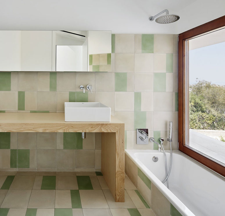 The combination of modern sustainable features and traditional materials create a welcome balance, while the green tiles link the minimalist space visually to the green nature outside