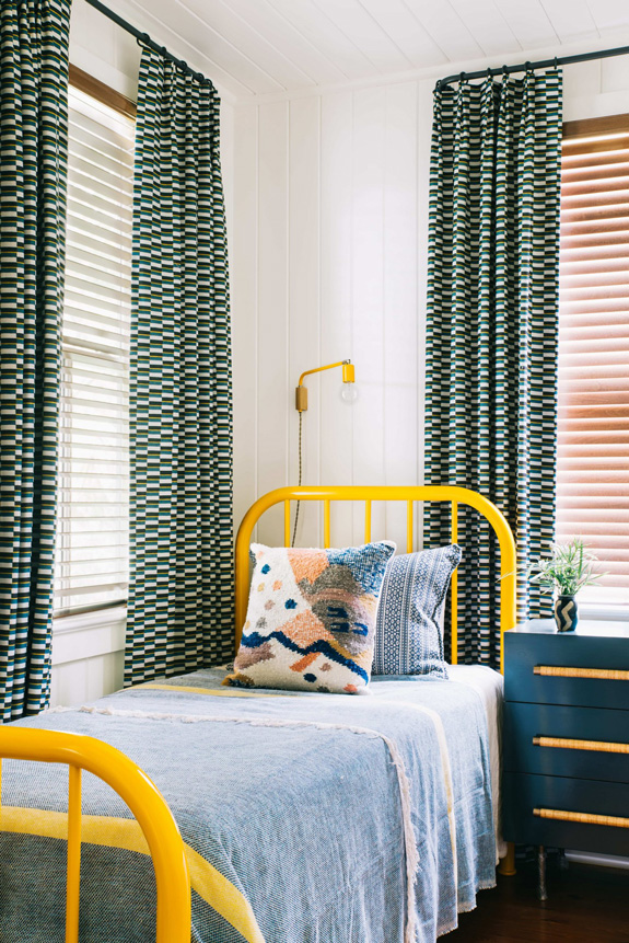 The guest bedroom is bolder and more colorful with yellow accents