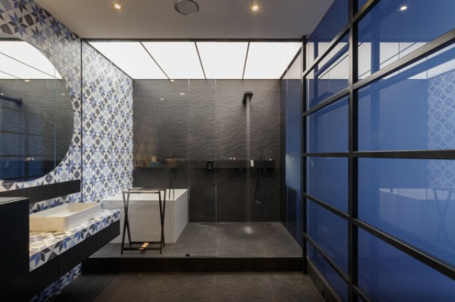 The shower fixtures match the color of the dark tiles behind it, which continue onto the floor of the bathroom