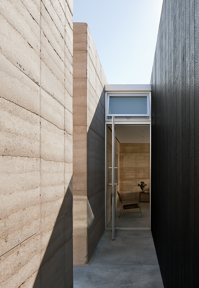 Excessive solar heat gain has been avoided by orienting the house on an east-west axis and by reducing door and window openings along these facades