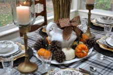 11 pinecones, tiny pumpkins and wheat for a centerpiece, black woven chargers and a plaid tablecloth and antique candle holders