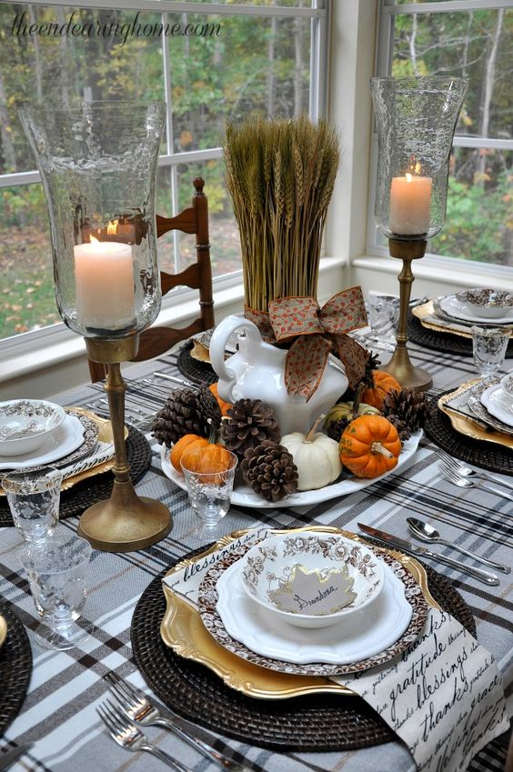 pinecones, tiny pumpkins and wheat for a centerpiece, black woven chargers and a plaid tablecloth and antique candle holders