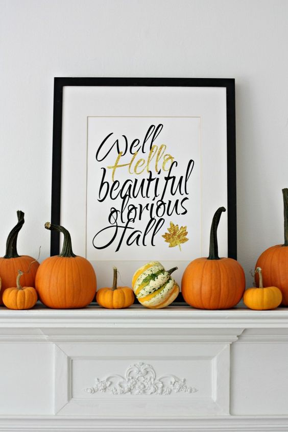 simple modern mantel with pumpkins and a framed artwork